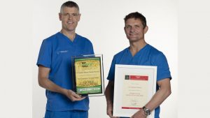 Dentists Steve & Patrick, holding up awards from OCM Dental Practice